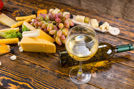 unlabelled: Gourmet Food Still Life - Close Up of Glass of White Wine with Fallen Bottle Amongst Variety of Cheeses and Fresh Fruit on Rustic Wooden Table with Copy Space