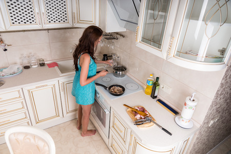 stove top: High Angle View of Brunette Woman Cooking in Kitchen - Young Woman Preparing Meal on Stove Top in Kitchen at Home
