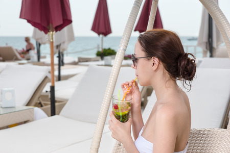 oceanfront: Young Woman in White Bikini Sipping Tropical Drink Through Straw While Sitting in Wicker Chair on Oceanfront Deck at Luxury Vacation Resort
