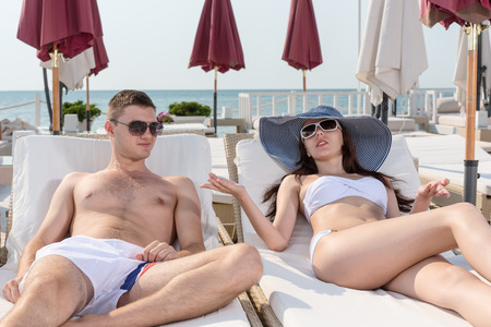 Young Couple in Summer Beach Fashion, Talking While Resting on Lounge Chairs In a Resort on a Sunny Climate.