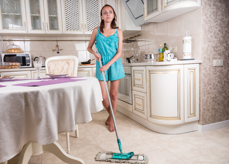 chores: Full Length of Young Brunette Woman Performing Household Chores by Mopping Floor in Clean Kitchen and Looking Off Into Space and Daydreaming
