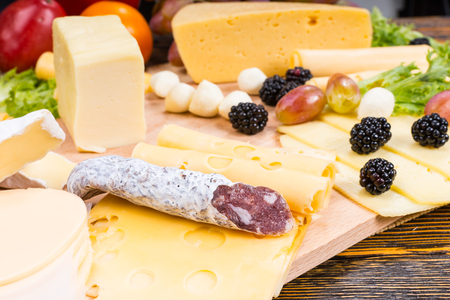 cheeseboard: Gourmet Cheese Board Featuring Variety of Cheeses, Cured Meat Sausage and Fresh Fruit Served on Rustic Wooden Table with Wood Grain