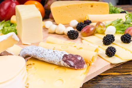 tabla de quesos: Tabla de quesos gourmet cuenta con variedad de quesos, Curado embutidos de carne y fruta fresca servida en mesa de madera rústica con madera del grano
