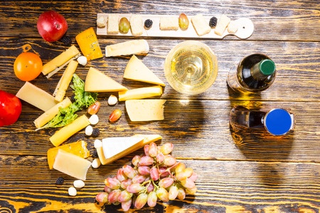 whiskey bottle: High Angle View of Gourmet Cheeses, Fruit and White Wine on Rustic Wooden Table with Copy Space Stock Photo