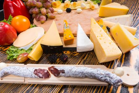 tabla de quesos: Picante salchicha seca curada y una tabla de quesos con un arreglo de una gran variedad de diferentes quesos en una mesa de buffet en un evento o fiesta atendidos Foto de archivo