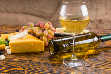 unlabelled: Gourmet Food Still Life - Glass of White Wine on Rustic Wooden Table with Fallen Bottle and Variety of Cheeses and Grapes