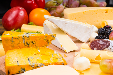 tabla de quesos: Selection of different cheeses on a platter with fresh salad ingredients and a bunch of grapes behind ready to be prepared and arranged on a buffet table