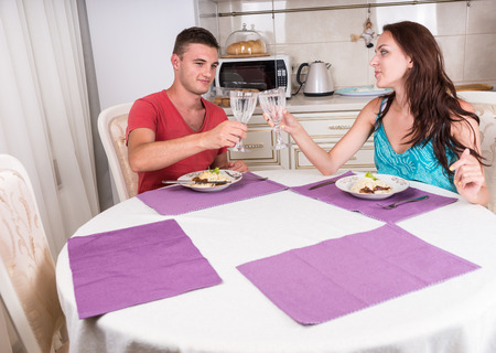 vasos de agua: Pareja joven tostaci�n con vasos de agua antes de comer comida casera en la Cena Hora mientras est� sentado en la mesa de comedor en las peque�as Cocina
