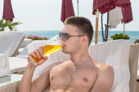 recliner: Young man enjoying a cold beer as he relaxes on a recliner chair at a coastal resort with the ocean behind him