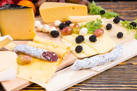 tabla de quesos: Tabla de quesos gourmet cuenta con variedad de quesos, Curado embutidos de carne y fruta fresca servida en mesa de madera r�stica con madera del grano