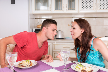 closer: Young Couple Having Romantic Dinner Together at Home - Man and Woman Sharing Single Spaghetti Noodle Getting Closer to Kissing
