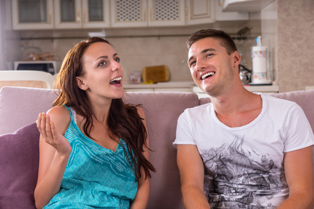 lighthearted: Close Up of Young Couple Having Light-Hearted Conversation Together While Sitting on Sofa in Living Room at Home