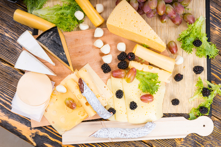 tabla de quesos: High Angle View of Gourmet Cheese Board Featuring Variety of Cheeses, Cured Meat and Garnished with Fresh Fruit, Served on Rustic Wooden Table