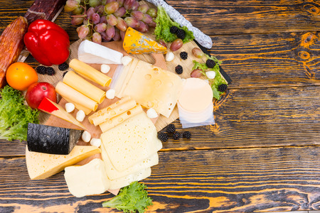 cheeseboard: Buffet display with a selection of different cheeses displayed on a wooden cheeseboard garnished with cocktail onions, olives, blackberries, grapes, tomato and peppers, overhead view with copyspace Stock Photo