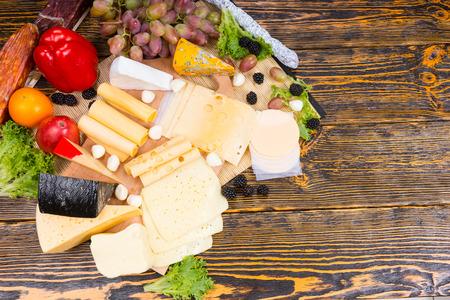 tabla de quesos: Pantalla buf� con una selecci�n de diferentes quesos que se muestran en una tabla de quesos de madera con guarnici�n de cebollas de c�ctel, aceitunas, moras, uvas, tomates y pimientos, vista a�rea con copyspace Foto de archivo