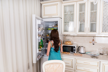 unidentifiable: Rear View of Unidentifiable Brunette Woman Standing in front of Open Refrigerator Door in White Kitchen at Home Stock Photo