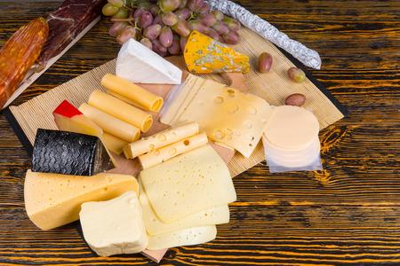 tabla de quesos: Vista elevada de la tabla de quesos gourmet con gran variedad de quesos y adornado con frutas, servidos en mesa de madera rústica con espacio de la copia