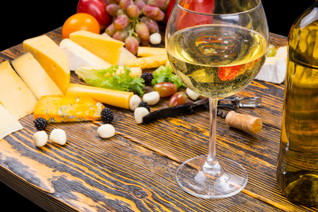 unlabelled: Gourmet Food Still Life - Close Up of Glass of White Wine Amongst Variety of Cheeses and Fresh Fruit on Rustic Wooden Table with Copy Space