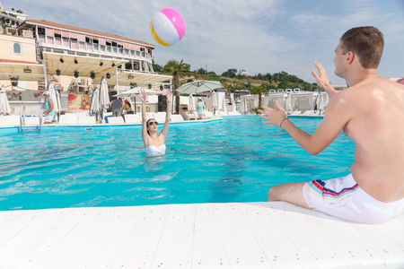 Young couple playing with a colorful plastic beach ball at a resort swimming pool throwing it to one another on a hot summer day