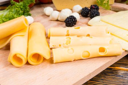 tabla de quesos: Rebanadas de quesos laminados clasificados en un quesos de madera listos para ser utilizados en una pantalla decorativa en una mesa de buffet en una fiesta Foto de archivo