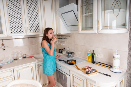 sautee: Young Brunette Woman Drinking Wine While Cooking Meat on Stove Top in White Kitchen at Home Stock Photo