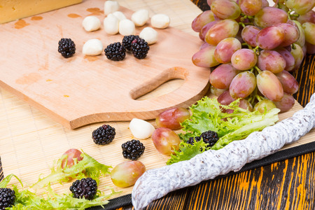 cheeseboard: Close Up of Wooden Boards with Bocconcini Cheese, Cured Meat and Fresh Fruit on Rustic Wooden Table with Wood Grain Stock Photo