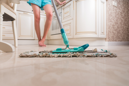 low angle view: Low Angle View of Young Woman Mopping Kitchen Floor with Focus on Shiny Clean Floor and Mop