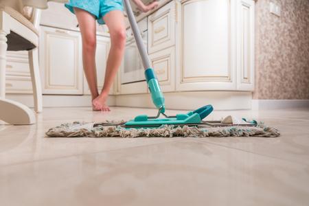 limpieza  del hogar: Vista de ángulo bajo de la mujer joven Mopping Cocina Pavimento con el foco en brillante Piso y fregona Limpiar