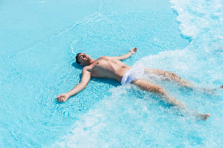 splayed: High Angle View of Young Man Wearing Swim Trunks Lying on Back with Arms and Legs Splayed in Shallow Waves of Swimming Pool on Sunny Day in Summer
