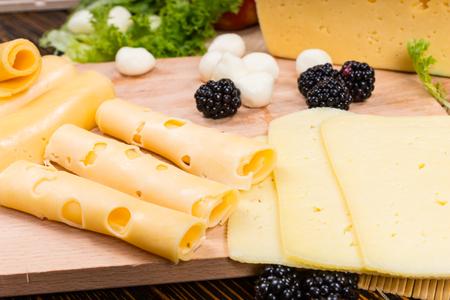tabla de quesos: La organizaci�n de las rebanadas de una variedad de quesos en una tabla de quesos con emmental laminado, cheddar y queso Gouda con mozzarella fresca y moras Foto de archivo