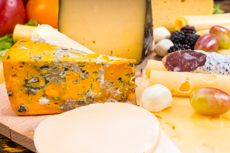 cheeseboard: Close Up of Gourmet Cheese Board Featuring Variety of Cheeses, Cured Meat and Garnished with Fruit - Detail of Appetizing Cheese Board