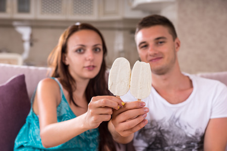 indulging: Young Couple Holding Ice Cream Bars Up to Camera and Sitting Together on Sofa at Home Stock Photo