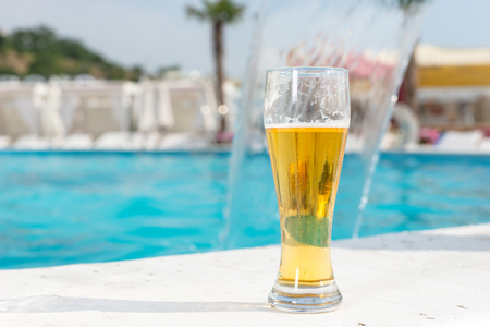 edge of the ice: Glass of ice cold beer standing on the tiles at the edge of a turquoise blue swimming pool at a tropical resort conceptual of a summer vacation