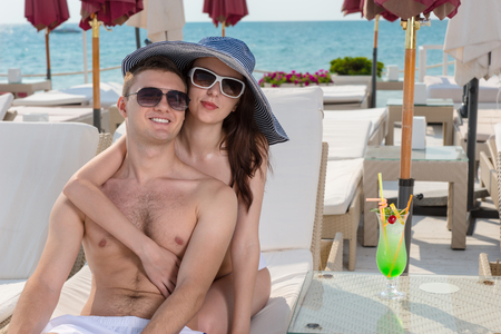 Loving young couple enjoying a summer vacation sitting relaxing in an intimate embrace at a tropical resort at the seaside on a recliner chair Stock Photo