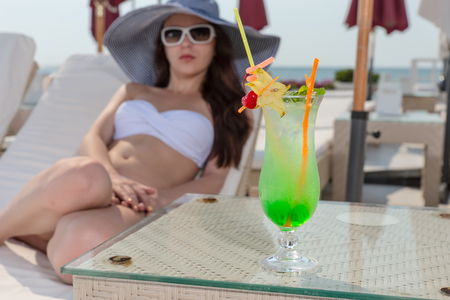 oceanfront: Young Woman on Vacation Wearing White Bikini and Large Sun Hat Relaxing on Lounge Chair on Sun Deck of Oceanfront Luxury Beach Resort, with Focus on Tropical Drink in Tall Glass Resting on Glass Table Stock Photo