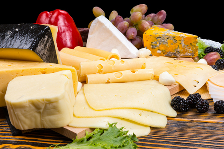 tabla de quesos: Selección Gourmet de quesos en una tabla de quesos con guarnición de moras frescas, aceitunas, uvas y pimiento rojo Foto de archivo