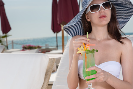 upmarket: Elegant young woman in a trendy sunhat and sunglasses sipping a tropical cocktail as she relaxes on the beach at an upmarket resort during a summer vacation