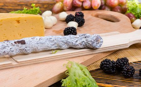 tabla de quesos: Secado chorizo ??curado listo para ser cortado en lonchas y se visualiza en una mesa de buffet con una variedad de quesos, moras, uvas y cebollas de cóctel
