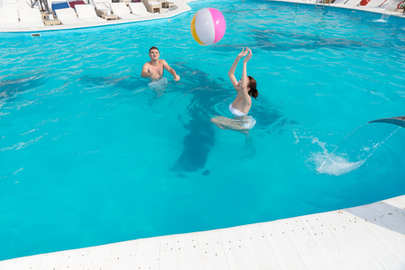 frolicking: Young couple frolicking in a turquoise blue swimming pool throwing a colorful beach ball to each other Stock Photo