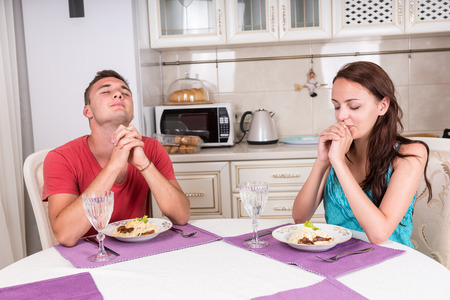 introspective: Young Religious Couple Saying Grace Prayer Prior to Eating Home Cooked Meal at Dining Table In Eat-In Kitchen of Small Home Stock Photo
