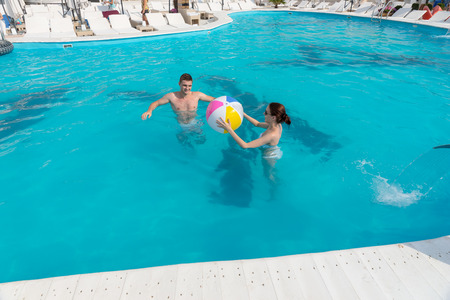 Young couple playing together in a resort swimming pool throwing a colorful beach ball to each other