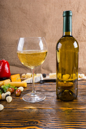 unlabelled: Close Up of Glass of White Wine with Bottle on Rustic Wooden Table Surrounded by Variety of Cheeses and Fresh Fruit