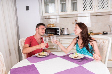 home cooked: Portrait of Young Couple Toasting with Water Glasses and Gazing at Each Other Before Eating Home Cooked Meal Together at Dining Table in Small Kitchen