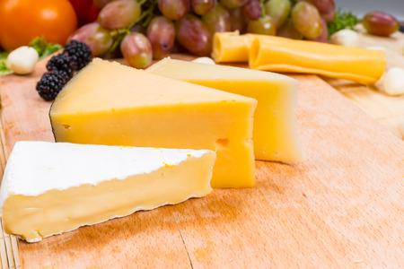 tabla de quesos: Variedad de diferentes cuñas de queso en una tabla de quesos de madera con uvas frescas, moras y un tomate en el fondo