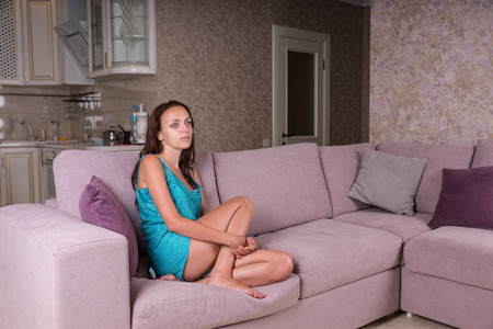 blank expression: Full Length of Young Brunette Woman Curled Up on Sofa in Living Room and Watching Television with Blank Expression at Home