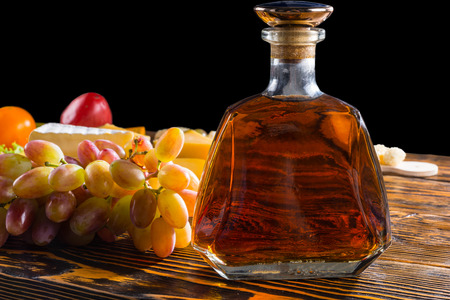 side lighting: Close Up of Bottle of Alcohol on Rustic Wooden Table with Variety of Cheeses and Grapes with Bright Side Lighting Stock Photo