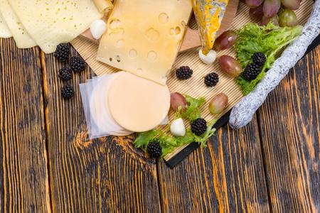 tabla de quesos: Opinión de alto ángulo de la Junta de queso gourmet cuenta con variedad de quesos y adornado con fruta fresca, servido en mesa de madera rústica con espacio de copia Foto de archivo