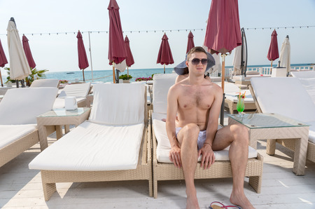oceanfront: Young Man Wearing Sunglasses Sitting on Edge of Lounge Chair on Deck of Oceanfront Luxury Beach Resort Stock Photo