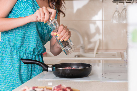 Young woman grinding pepper onto cooking meat in a frying pan on the stove using a large pepper mill, close up of her hands