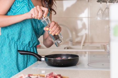 Junge Frau Schleifen auf dem Herd Pfeffer auf Kochen von Fleisch in einer Pfanne eine große Pfeffermühle, in der Nähe ihrer Hände